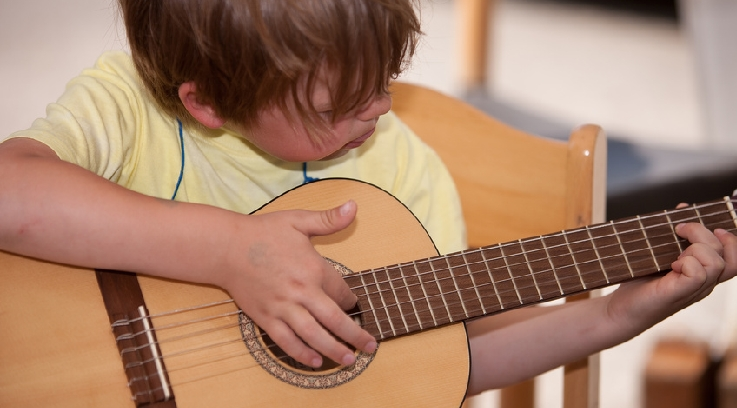 Ein Junge übt auf der Gitarre. Bild: Fotolia, Thomas Scherr