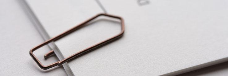 Festgehalten: Eine Büroklammer fasst verschiedene Papiere zusammen. Foto: fotolia.com