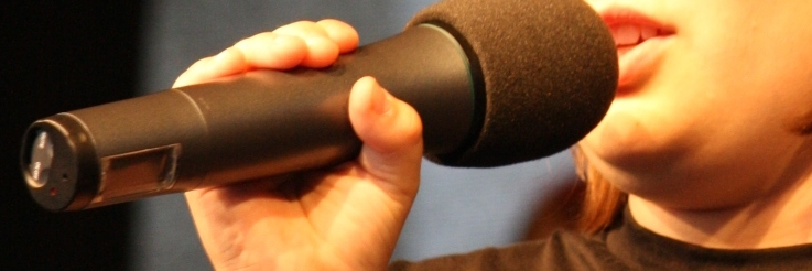 Eine Sängerin singt ins Mikrofon