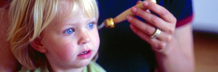 Ein Kind lauscht aufmerksam dem Geräusch eines Glöckchens